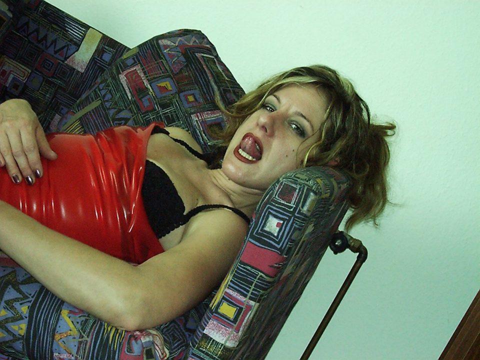 Frau im Latexshirt streckt ihre Zunge Raus